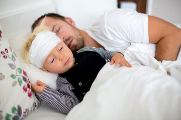 Little toddler boy with head injury, lying with dad in bed