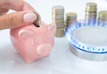 Female hand with coin and piggy bank near the flame of a gas stove in the kitchen. Symbolic image of cost, energy efficiency and saving natural gas at home.