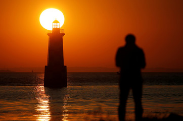 """A photographer takes a picture during sunrise over """"La Perdrix"""" lighthouse in Loctudy"""