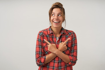 Happy attractive woman with bun hairstyle looking upwards, crossing hands on her chest and pointing with forefingers to different sides and smiling widely
