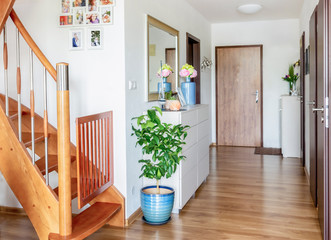 Fototapeta home hallway with wooden floor, white furniture and mirror