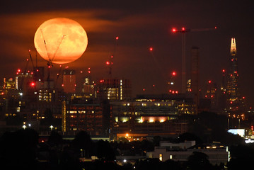 The full moon is seen rising above the London skyline, London, Britain