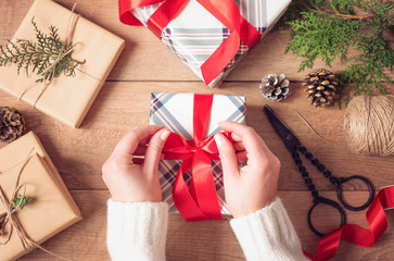 Christmas Background. Female Hands Tying A Red Bow. Woman Packing Christmas Gifts. Holiday Concept. Top View, Flat Lay, Advent Gift