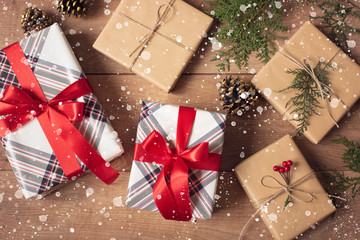 Christmas Background. Top View Of Christmas Boxes And Lights In Craft And Red Stripe Paper Decorated With Branch, Linen Cord, Red Bow On Wooden Table. Drawn Snow