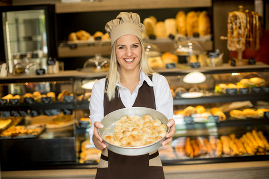 Young woman holding basket with pastry at her bakery smiling joyfully to the camera
