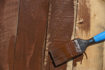 A paintbrush on wood covered in brown paint