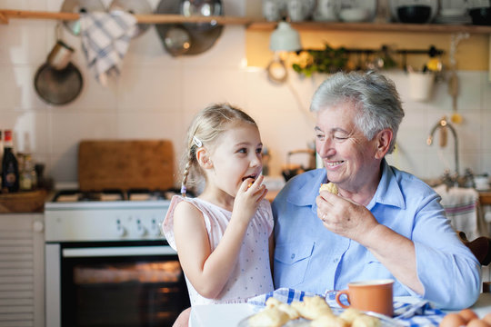 Child girl and senior woman are eating cookies in cozy kitchen at home. Happy family is enjoying handmade pastries. Grandmother and funny kid are tasting delicious food.