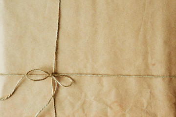 Overhead view of a single holiday package wrapped with eco friendly craft paper and tied with twine.