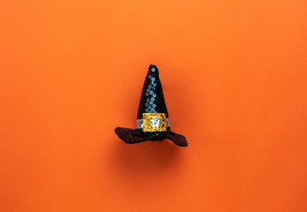 Table top view aerial image of Happy Halloween decorations festival concept background.Flat lay accessories essential object to party the black hat of witch on modern rustic orange paper.