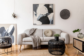 Stylish and scandinavian living room interior of modern apartment with gray sofa, pillows, plaid,...