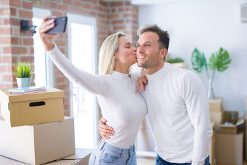 Young beautiful couple standing using smartphone to take selfie kissing at new home around cardboard boxes
