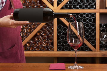 concept of tasting and buying wine, a girl pours wine in a glass, against the background of a rack with bottles