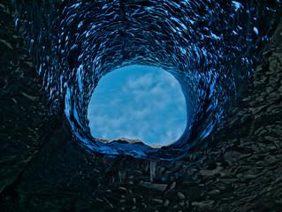 Eine große Öffnung in einer blauen Gletscherhöhle