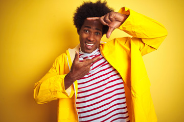 African american man with afro hair wearing rain coat standing over isolated yellow background smiling making frame with hands and fingers with happy face. Creativity and photography concept.