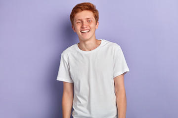 Portrait of young happy attractive man , wearing a white t-shirt, smiling and looking at the camera isolated over blue background.people, lifestyle