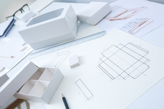Development design drawing packaging. Desktop of a creative person making cardboard boxes.