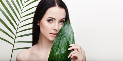 Portrait of young beautiful woman with healthy glow perfect smooth skin holds green tropical leaf....
