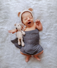 Top view of sleepy newborn boy wrapped in gray scarf and with little cap hugging knitted bear and...