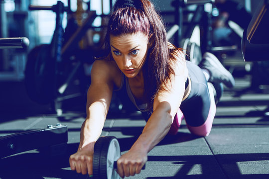 Focused beautiful Caucasian muscular woman in sports clothing and with ponytail doing exercises for abs with ab roller wheel in gym.