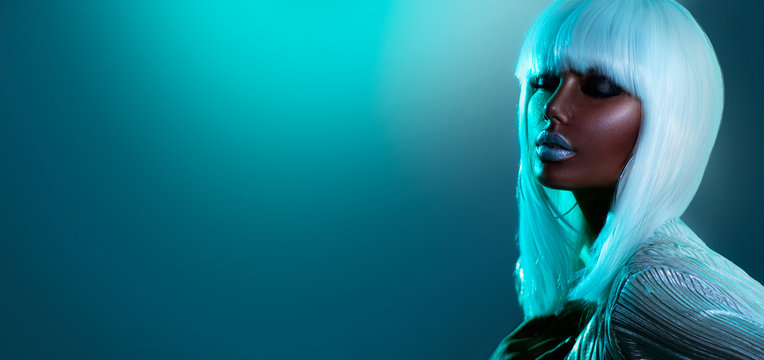 High Fashion model girl in colorful bright neon lights posing in studio, portrait of beautiful woman in white hair, wig and silver trendy glowing make-up. Glitter neon bright makeup