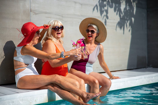 Joyful old women toasting with cocktails stock photo