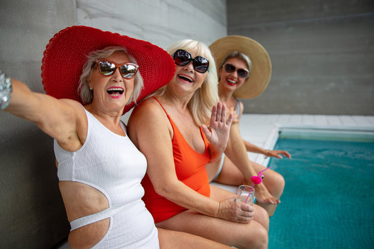 Cheerful old women in swimsuits making selfie