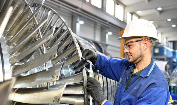 workers manufacturing steam turbines in an industrial factory