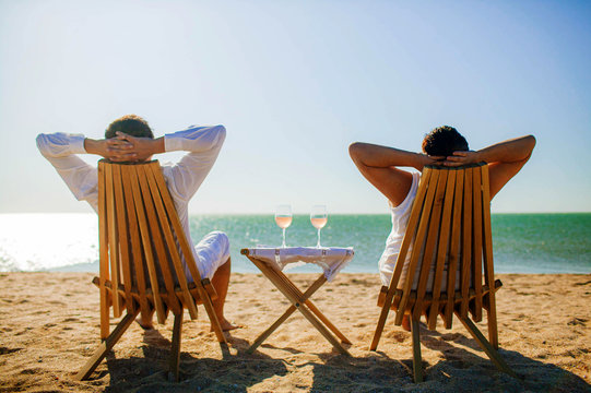 holidays, leisure and people concept - view from the back of happy senior couple relaxing with wine glasses on summer beach.