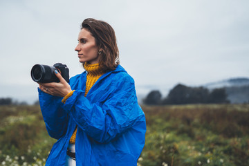 photographer girl in blue raincoat hold in hands photo camera take photography foggy mountain, traveler shoot autumn nature, video click on camera technology, landscape vacation concept free space
