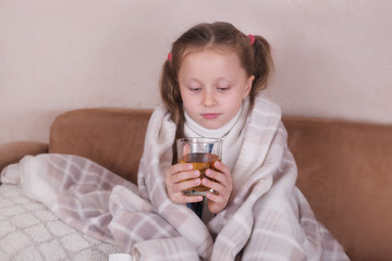 Child taking medicine. Sick girl with scarf lying on bed