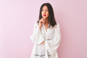 Young chinese woman wearing summer shirt standing over isolated pink background with hand on chin thinking about question, pensive expression. Smiling with thoughtful face. Doubt concept.