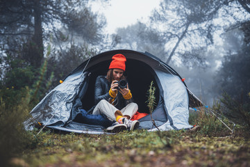 Wall Mural - photographer tourist  take photo on camera in camp tent on background foggy rain forest, hiker woman shooting mist nature trip, trekking tourism, rest vacation concept camping holiday, copy space