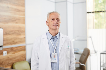 Waist up portrait of senior doctor looking at camera while posing standing in office of modern...
