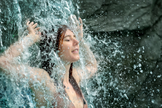 young sexy woman with red hair enjoys the falling water of the waterfall