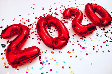 2020 happy new year in the form of red balloons isolated on white background. scattered confetti on a white background. Christmas card. gel balls in the form of numbers 2020. holiday atmosphere.