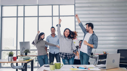 group of creative designer dancing in office with relax feeling and glad about good success news of...