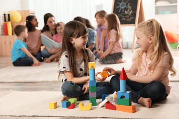 Cute girls playing with building blocks on floor while kindergarten teacher reading book to other children indoors