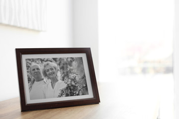 Portrait of senior couple in frame on table indoors. Space for text