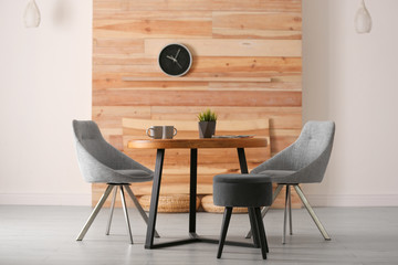 Stylish room interior with round table and comfortable chairs