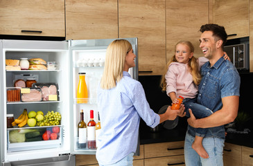 Happy family with bottle of juice near refrigerator in kitchen