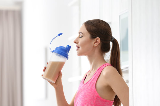 Athletic young woman drinking protein shake in kitchen