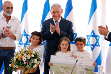 Israeli Prime Minister Benjamin Netanyahu applauds as he is presented with a gift from Israeli residents of the area, at the start of a weekly cabinet meeting in the Jordan Valley, in the Israeli-occupied West Bank