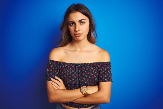 Young beautiful woman wearing floral t-shirt over blue isolated background skeptic and nervous, disapproving expression on face with crossed arms. Negative person.