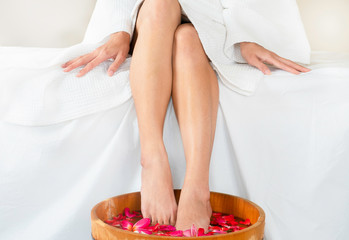 Woman soaking feet in wooden spa bowl of water with floating flowers at spa.