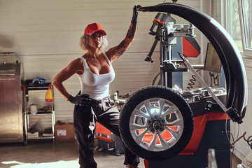 Attractive brave woman is posing for photographer at auto workshop with part of car.