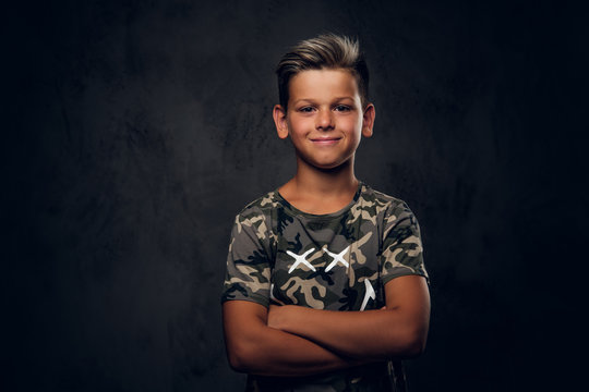Little charming boy with nice hairstyle is posing over dark background at photo studio.