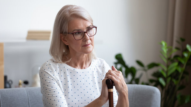 Upset mature woman holding wooden cane, thinking about future