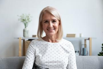 Head shot portrait smiling mature woman looking at camera