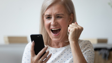 Close up excited older woman shouting, using phone, celebrating success