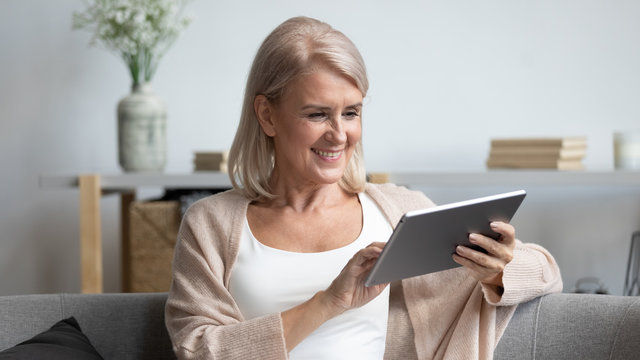 Smiling mature woman using computer tablet apps, having fun